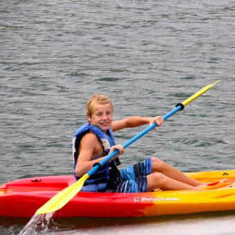 A boy smiles while kayaking through Murray Harbor's Lake Murray boat rentals
