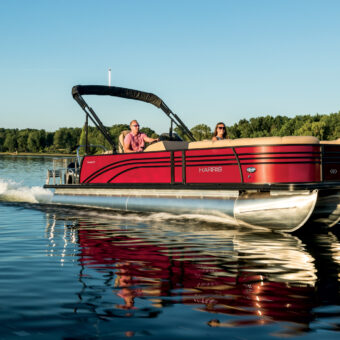 This cherry red Sunliner boat cruising across the water is one of many Lake Murray boat rentals to be found at Murray Harbor.