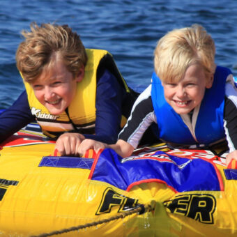 Two children smile while being pulled on a bright yellow tube.