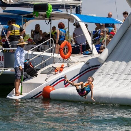 A little boy laughs as he slides down an inflatable slide with State Park Marina.