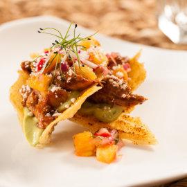 Mole duck taco with puffed rice avocado cilantro puree and pineapple radish salsa and cotija
