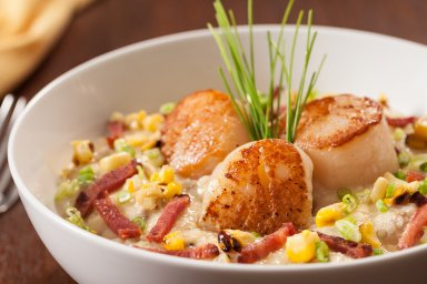 Duck fat seared scallops over cheddar duck corn grits