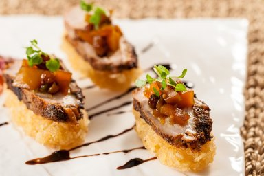 Roasted duck on crispy rice cake with spicy mango chutney
