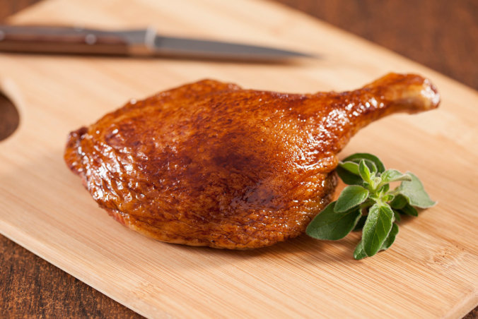Single duck leg on cutting board