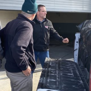 Officers helping unload gifts brought to hand out to inmates for Christmas Behind Bars through the volunteers at The ROP Shop and Outdoor Concepts.