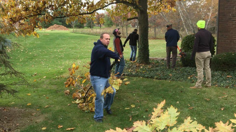 Men doing yard work and tree trimming.