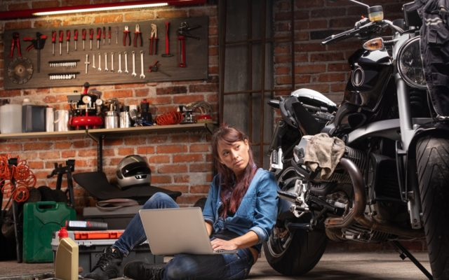 Woman sitting next to her motorcycle with her laptop ordering parts