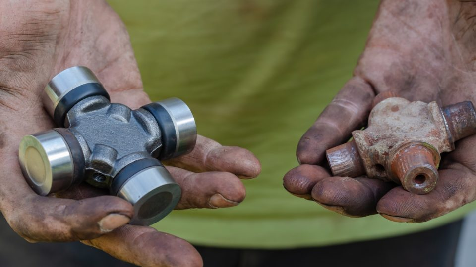 Man holding a new and a used part