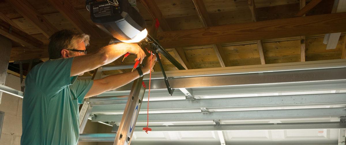 Man on a ladder fixing a garage door