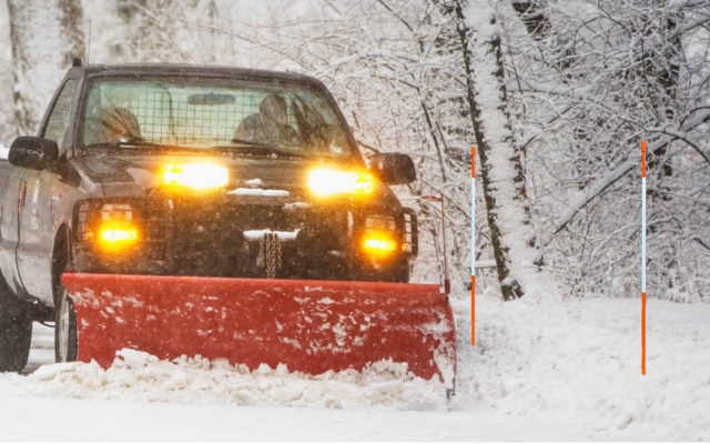Snowplow moving snow near driveway marker snow stakes.