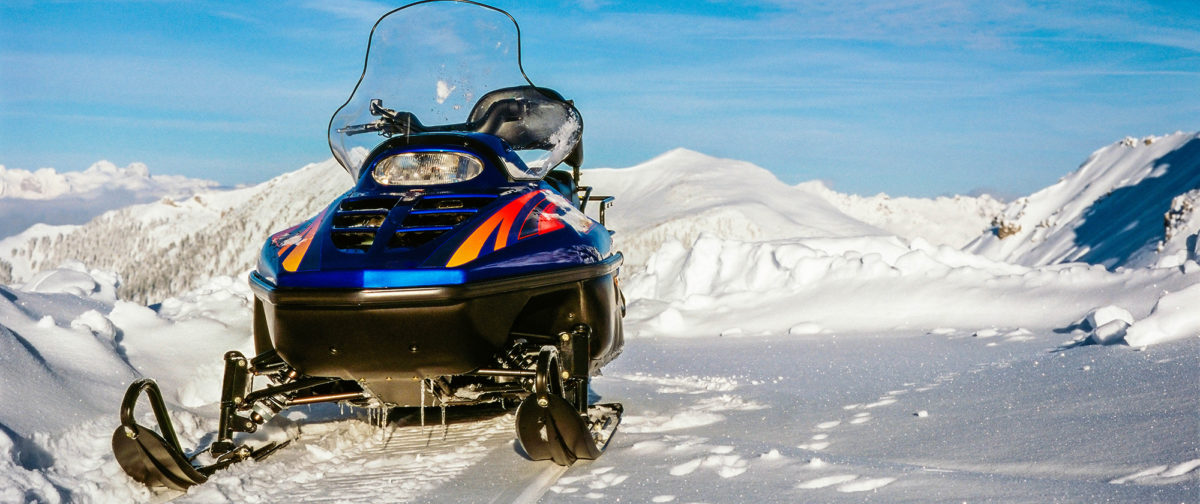 Snowmobile unmanned in the snow.