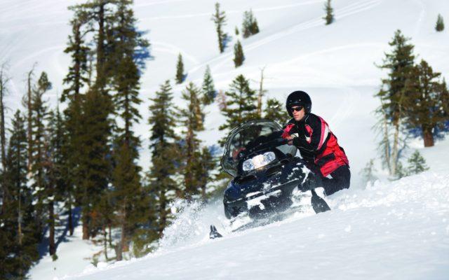 Man pushing his snowmobile that wont start