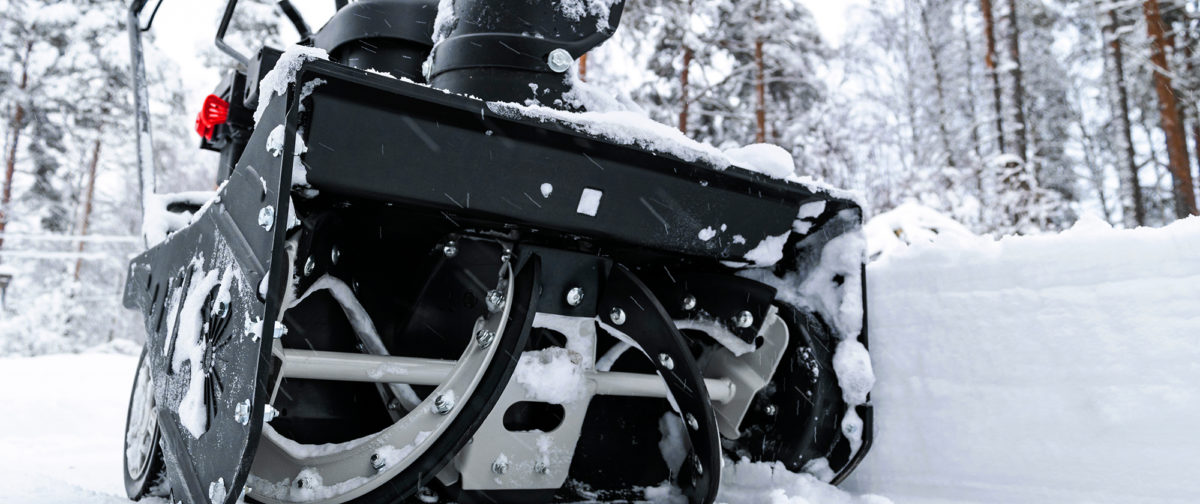 A snow thrower sits in the snow.