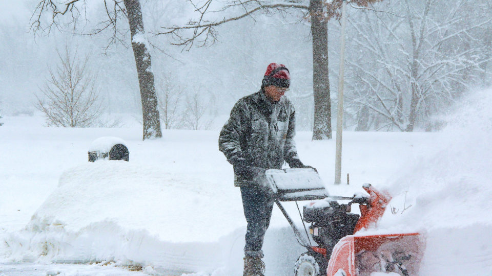 A man pushing a snowblower as it throws out snow.