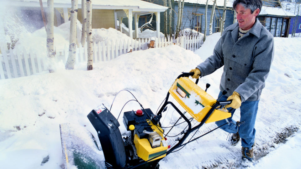 A man pushing a yellow snowblower as it throws out snow.