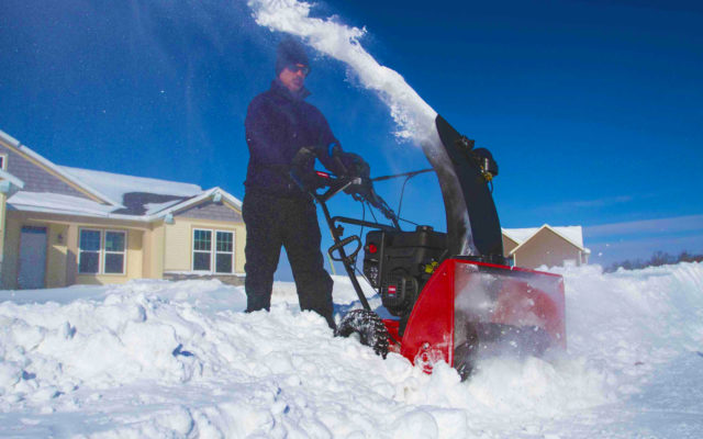 A man clearing a path through snow with his snowthrower.