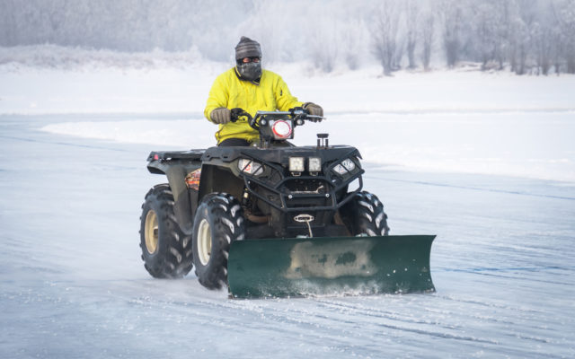 Man with a plow attachment on his ATV.