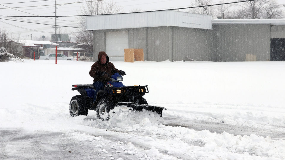 Man plowing snow on his ATV
