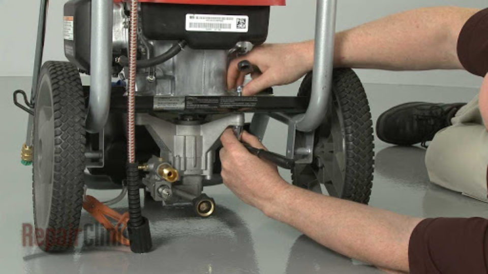A man bolting down a power pressure washer pump from The ROP Shop.