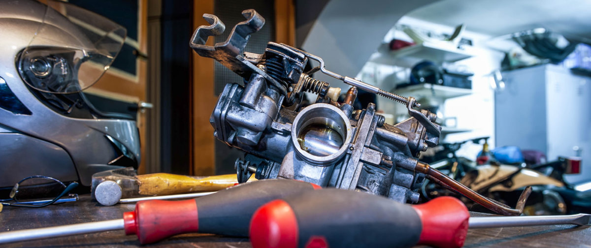 Image of a carburetor being worked on.