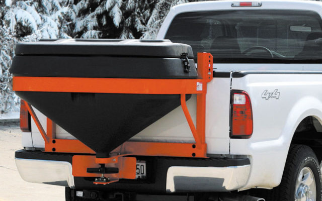 Truck using a salt spreader system in winter time.