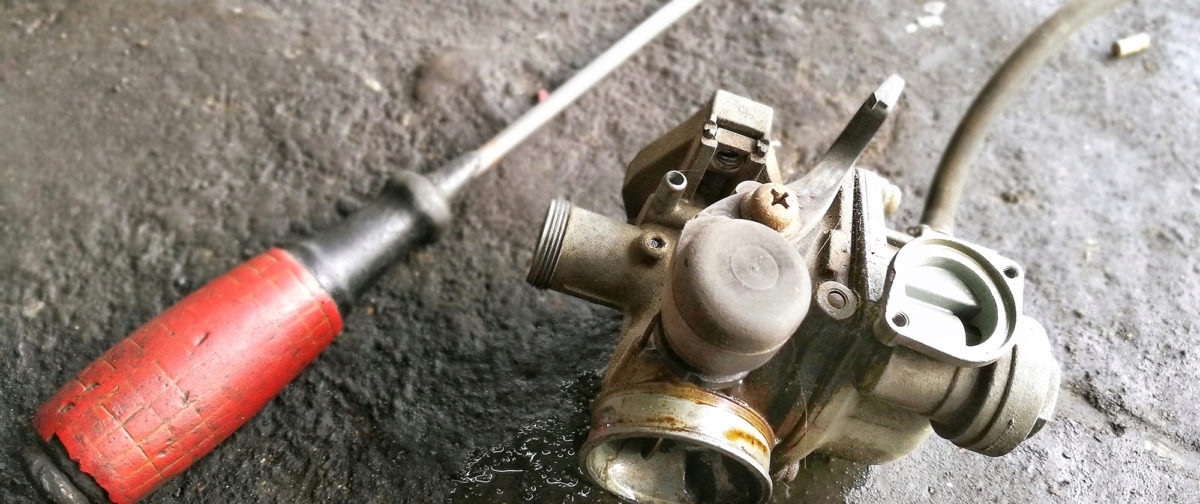 A used carburetor on a concrete floor next to a screwdriver.