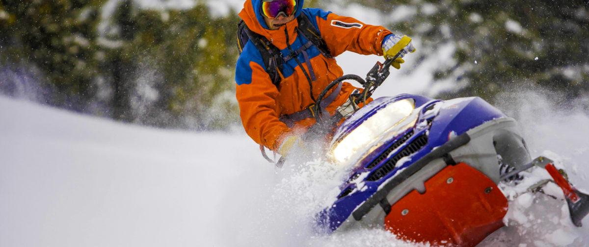 A man riding a snowmobile through the snow.