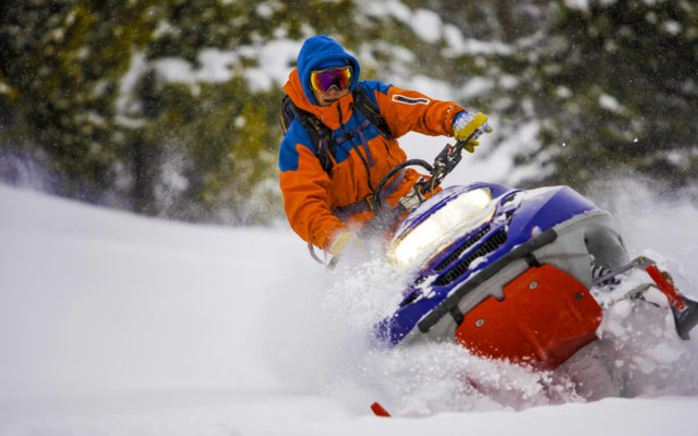 A man riding a snowmobile through the snow.