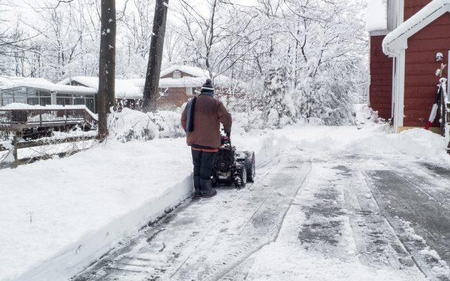 Man clearing his driveway of snow.