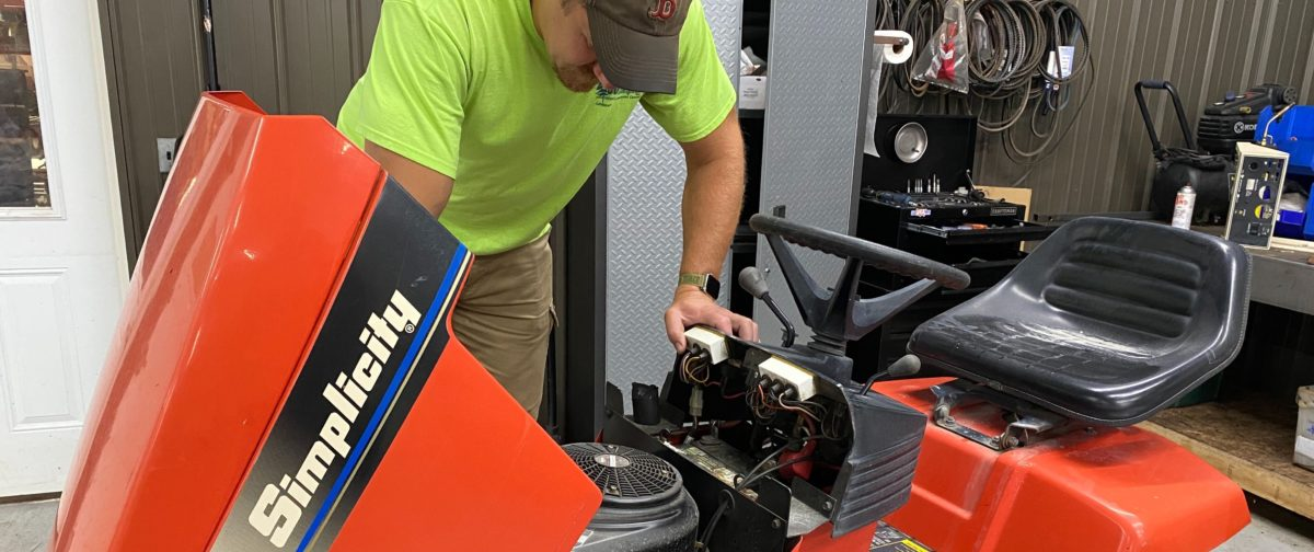 A man working on a riding lawnmower.