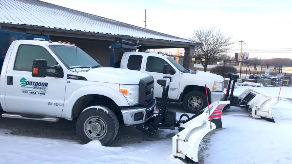 Two Outdoor Concepts trucks with snowplow attachments.