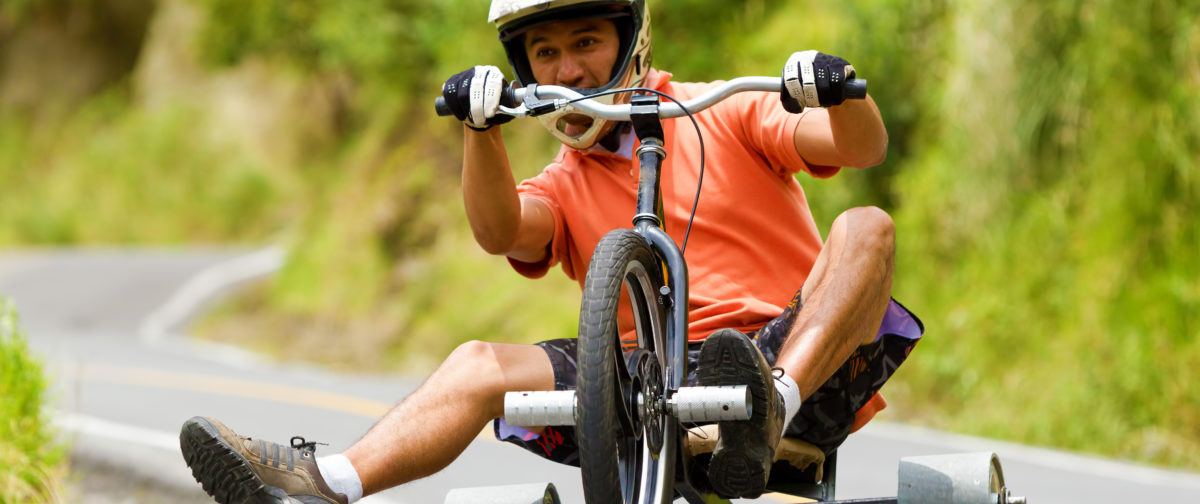A guy drifting down hill on a gravity driven drift trike