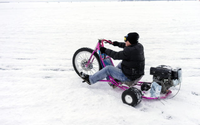 Guy riding a drift trike on snow