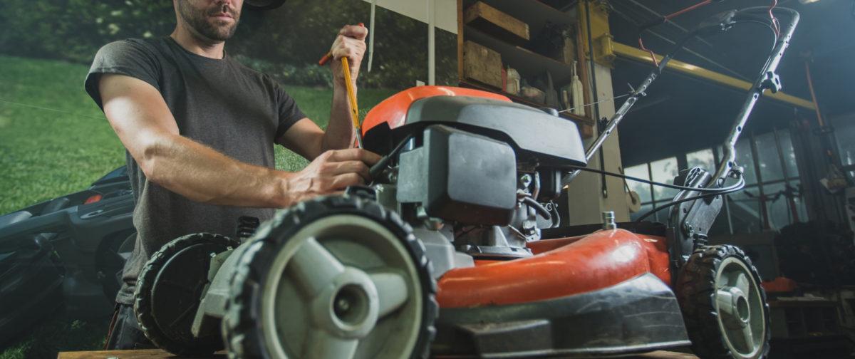 A man repairing a push mower.