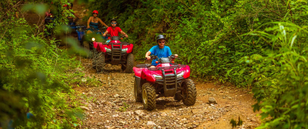 A family rides ATVs down a dirt path through the woods.