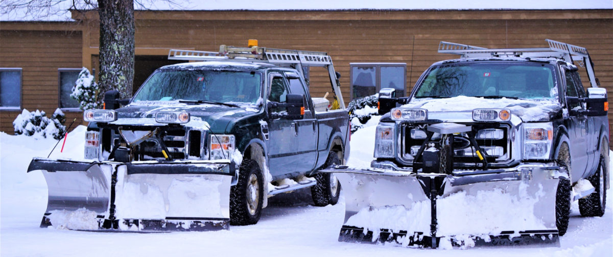 Two plows covered in snow in front of a building with snow on the ground.