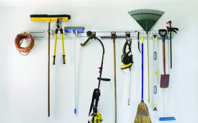 A wall in a garage with tools hanging up.