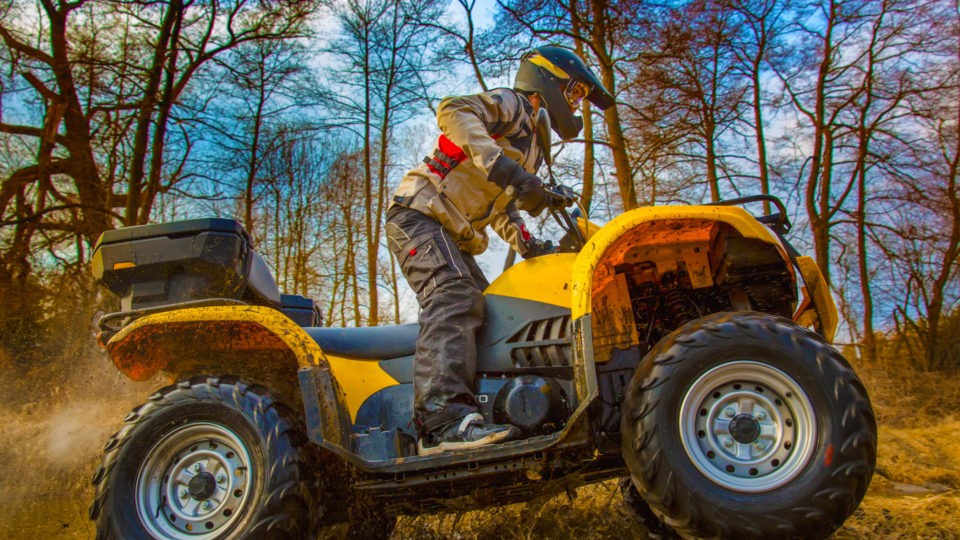 A child wearing safety gear on an ATV, traveling uphill through the woods.