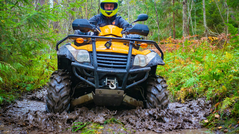 A kid in safety gear driving his ATV through a muddy and water filled path in the woods.