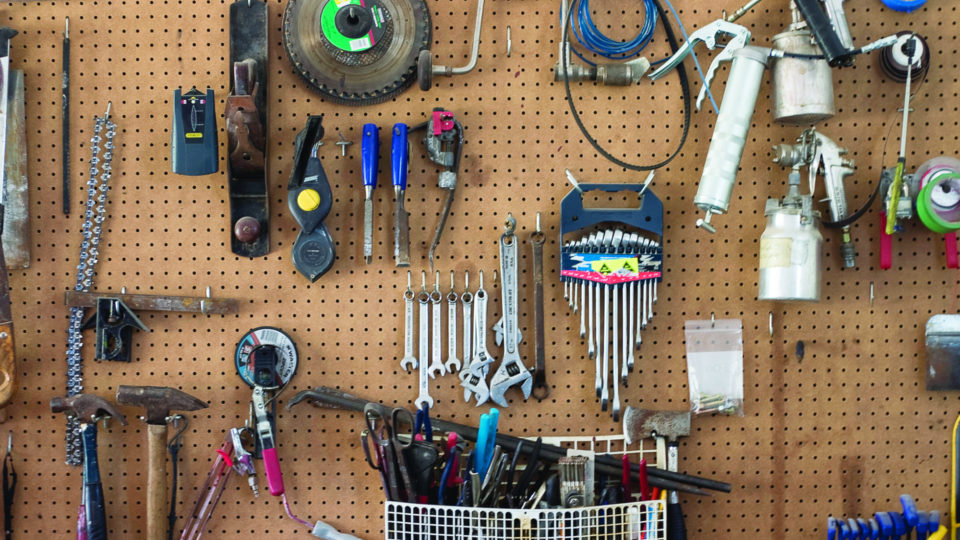 A wall of hanging tools in a garage.