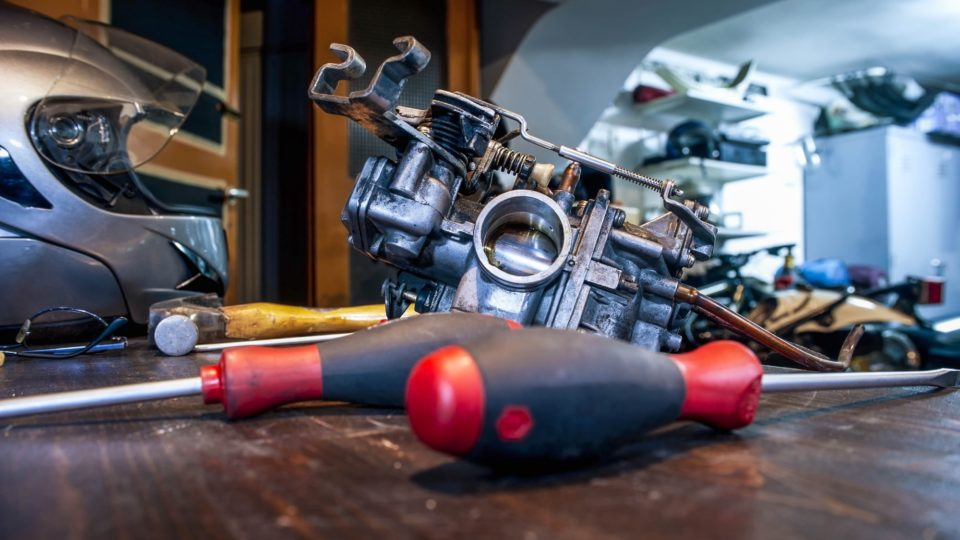 A motorcycle helmet, carburetor, hammer and two screwdrivers sit on a table next to a motorcycle.