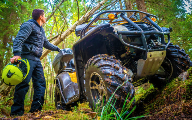 A man stands next to his ATV in the middle of the woods.