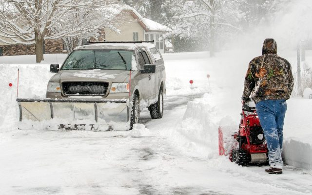 Snowplow and snowthrower pass each other on a snowy road