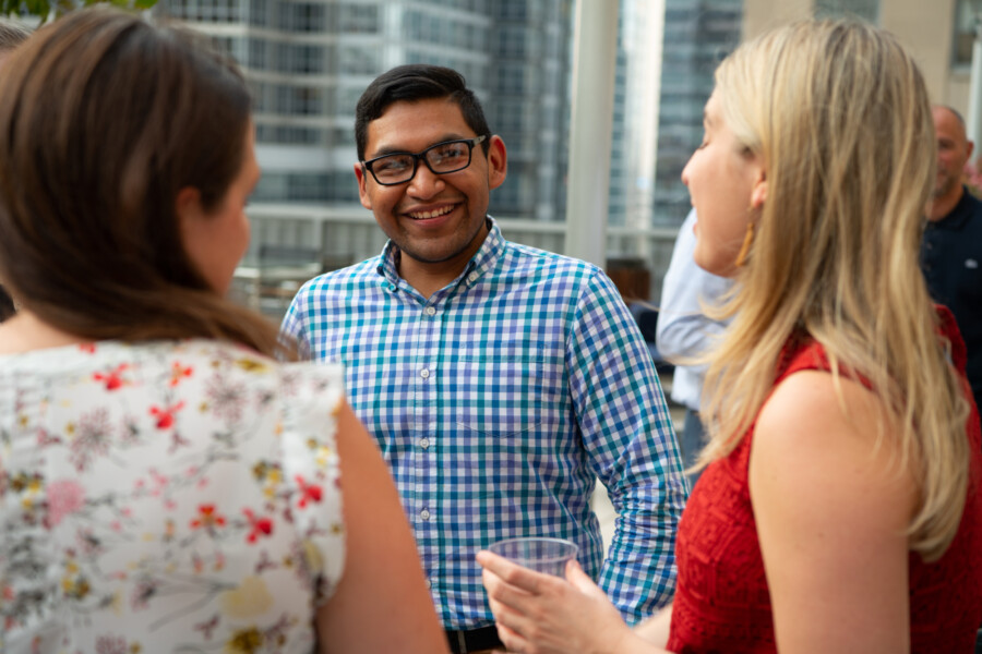 Man speaking with two women at an event
