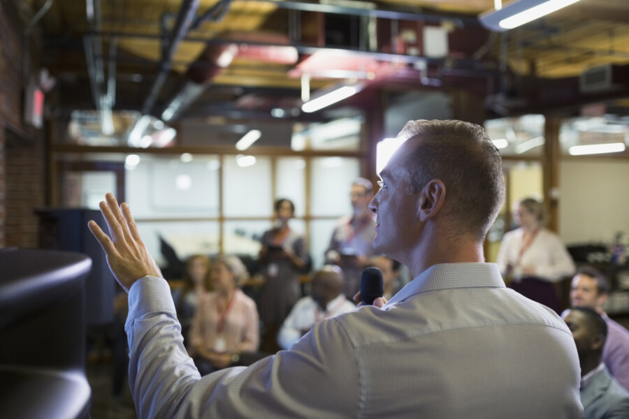 Man presenting to a group while pointing at something
