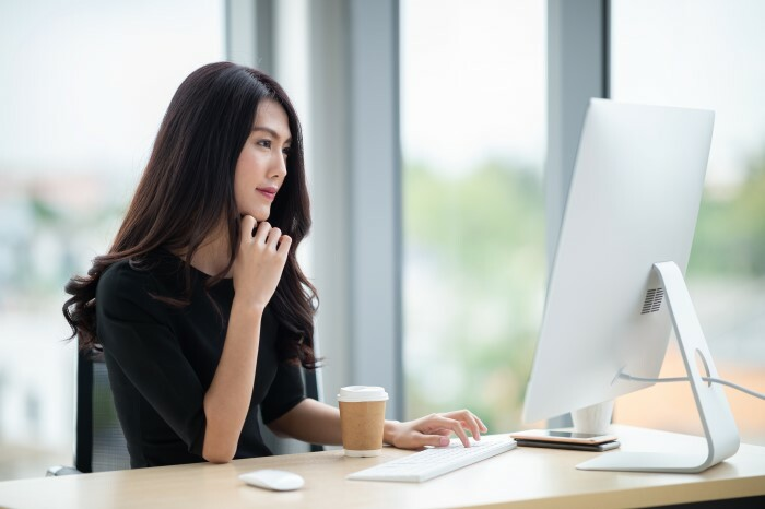 Woman sitting in front of computer with a cup of coffee.