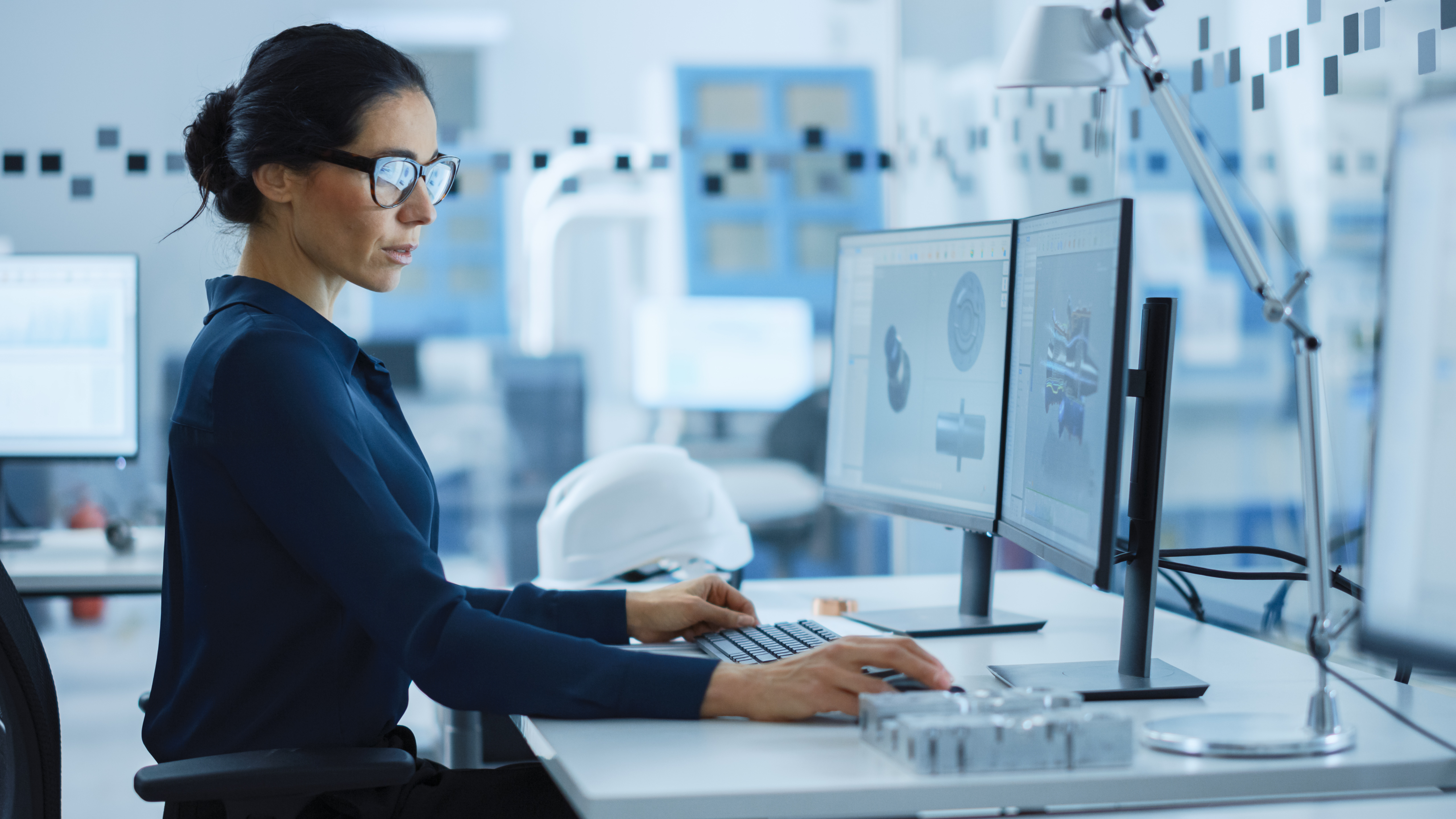 Woman sitting at desk with two monitors