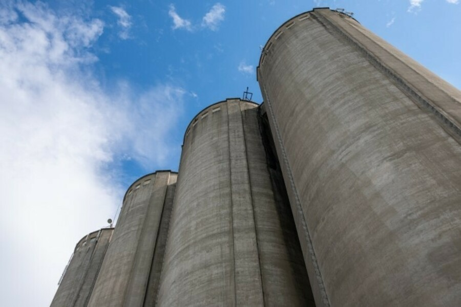 Four concrete silos with the clouds above them.