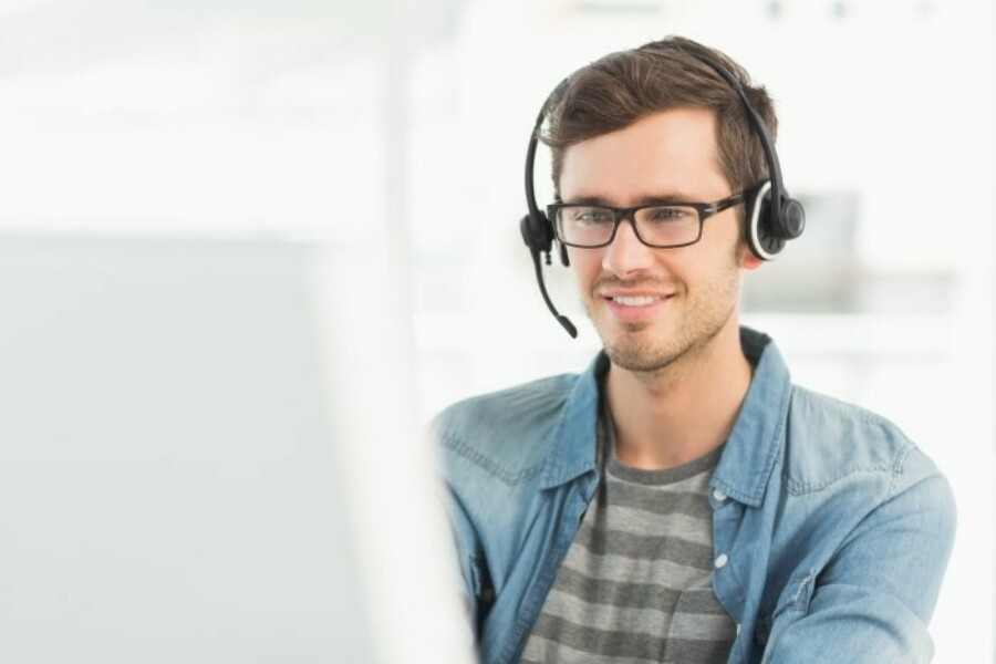 Young man with headset sitting in front of computer
