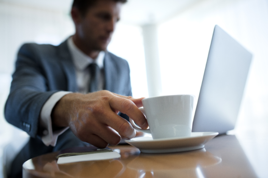 Man in a suit reaching for a cup of coffee as he works on laptop